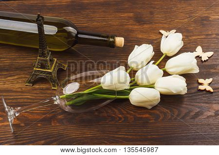 Wineglass with bouquet of white tulips on the wooden background