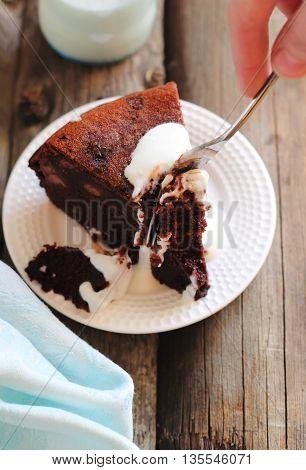 cutting a piece of chocolate cake with a banana garnished with yogurt