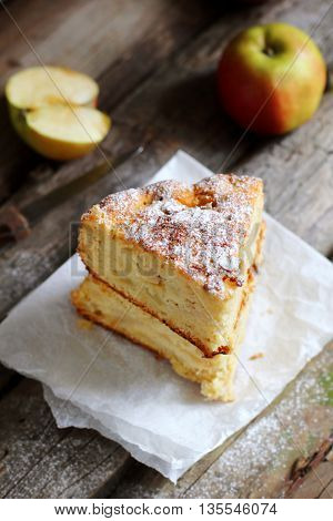two pieces of homemade apple pie on a wooden background