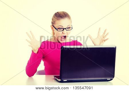 Young surprised woman sitting in front of laptop.