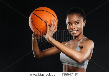 Portrait of happy woman in sportswear holding basketball isolated on the black background
