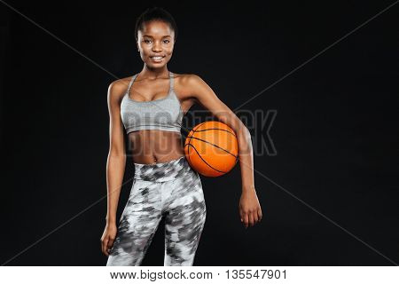 Happy beautiful sports woman holding ball isolated on the black background