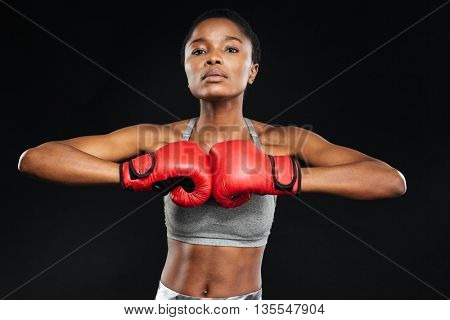 Beautiful fitness woman posing with boxing gloves on black background