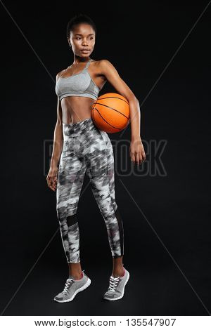 Full length portrait of a sports woman holding basketball ball isolated on a black background
