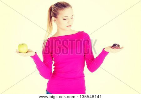 Young casual woman holding an apple and cookie.