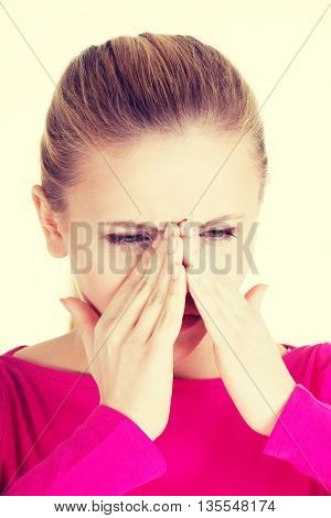 Young caucassian woman is having sinus pressure.