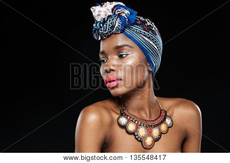 Close-up portrait of an attractive afro american woman looking away isolated on the black background