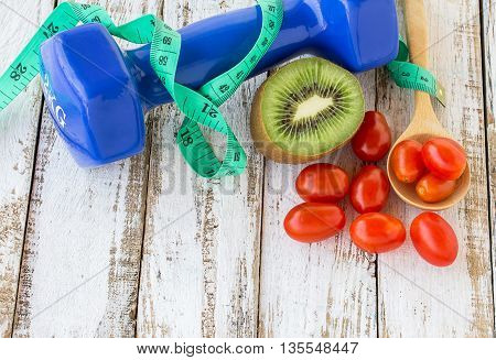 Fresh kiwidumbbell and red tomatos on white wooden table background