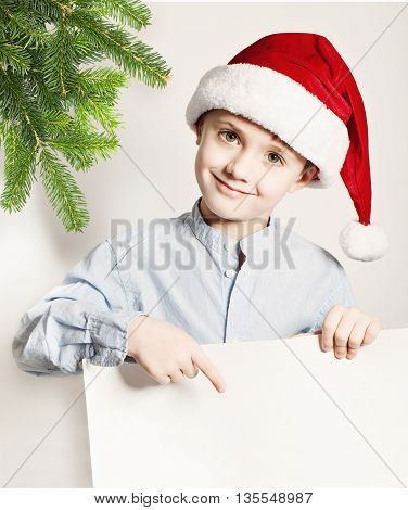 Christmas Concept. Child Boy in Santa Hat Showing White Banner Background. Smiling Little Boy Xmas Tree Twig and Blank Paper
