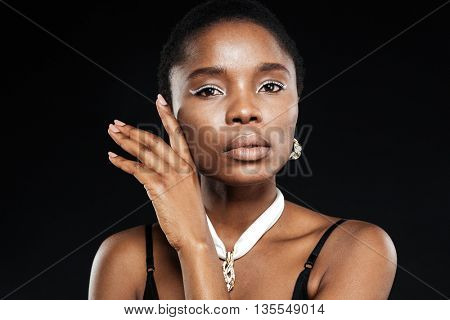 Close-up portrait of a beautiful attractive ethnic african woman isolated on the black background