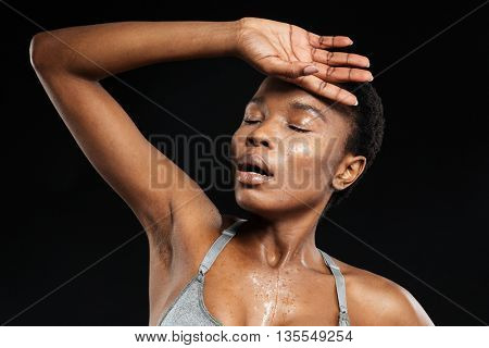 Portrait of a fitness afro american woman posing isolated on a black background