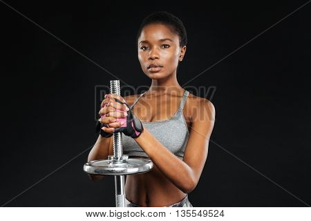 Close-up portrait of a young fitness girl doing exercises with barbell at the gym isolated on a black background