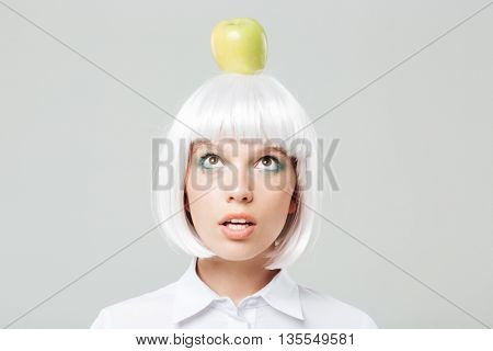 Portrait of funny cute young woman with apple on her head