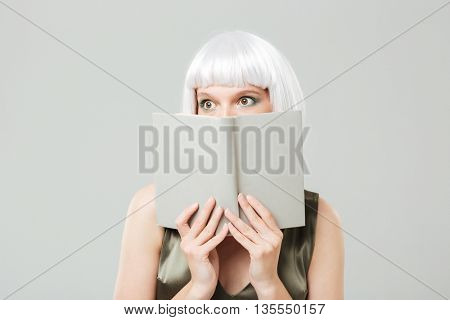 Scared pretty young woman covered her face with book