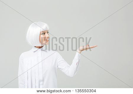 Happy attractive young woman with blonde hair holding copyspace on palm