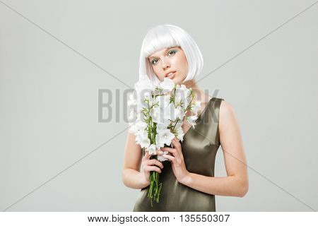 Portrait of sensual attractive young woman with bouquet of flowers