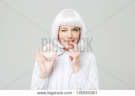 Charming playful young woman winking and holding donut