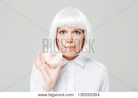 Confused beautiful young woman holding sweet donut