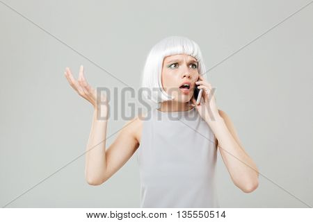 Puzzled worried young woman in blonde wig standing and talking on mobile phone over white background