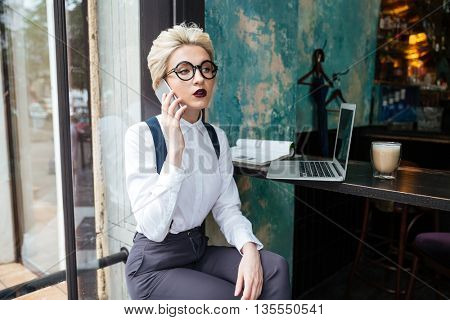 Candid image of a businesswoman working in a cafe working with laptop