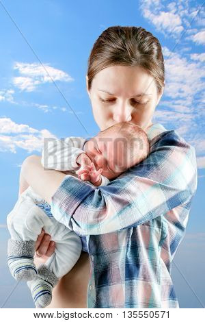 mother stands and holds the newborn baby outdoor shoot.