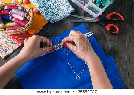 The woman hands sewing the clothing on dark rustic Wood Background