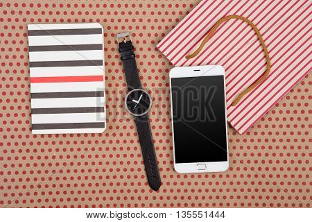 Handmade Striped Shopping Bag, Gift Bags, Notepads, Watch And White Smartphone On Craft  Paper Backg
