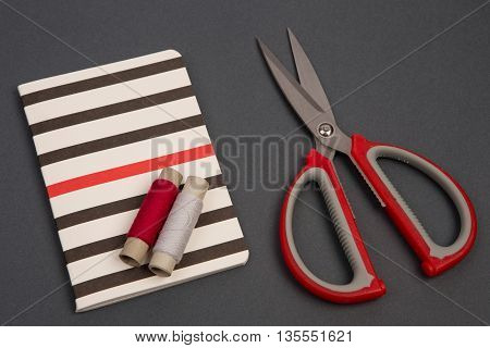 Grey And Red Thread, Scissors And Striped Notepad On Grey Background