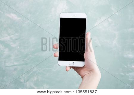 Touch Screen White Smartphone With Black Screen In Boy Hand On Green Background