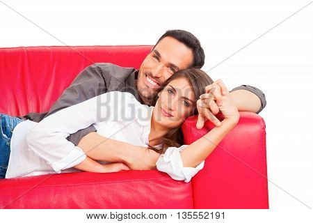 Portrait of romantic couple relaxing on sofa. Happy loving male and female partners are holding hands. They are spending leisure time on white background.