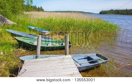 Small Rowboats Lay On Coast Of Still Lake
