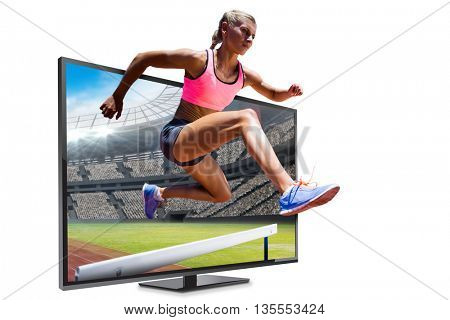 Sporty woman jumping a hurdle against view of a stadium