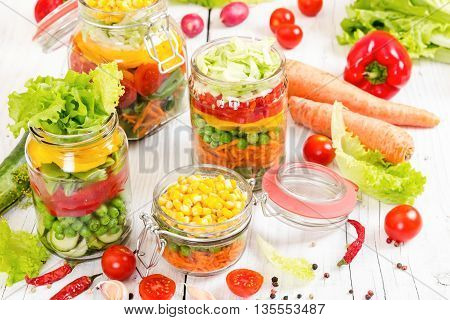 Colorful Vegetables In Glass Jars On Wooden Background.