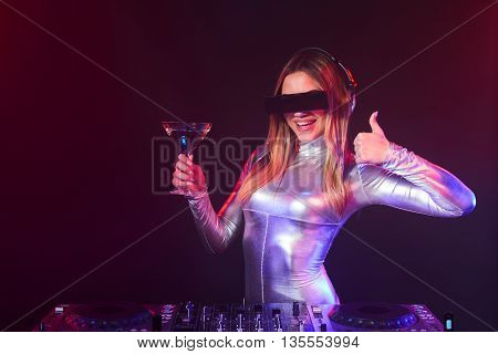 Happy DJ girl on decks at the party wearing silver coverall holding a glass with cocktail and gesturing thumb up