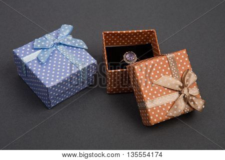 Gift Boxes In Polka Dots With Silver Diamond Vintage Wedding Ring On Grey Background