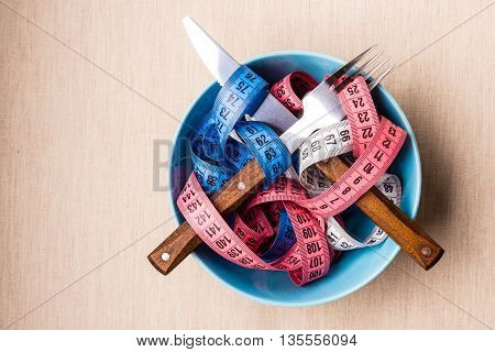 Diet food healthy lifestyle and slim body concept. Many colorful measuring tapes in blue bowl on table with knife and fork top view