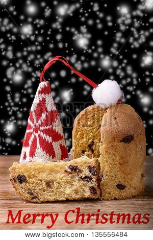 chocolate panettone sliced on wood traditional dessert for christmas in Italy and hat of santa claus, snow and merry christmas written