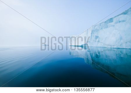 blue glacial ice in crystal clear water. Glaciers and icebergs