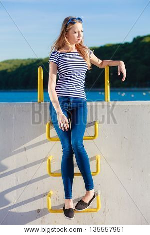 Young blonde woman in full length casual style against stone wall sea in the background