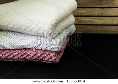 Neatly Folded Sweaters On A Wooden Background