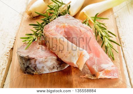 raw carp steak with rosemary and spring onions on wooden board