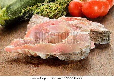 raw carp steak on a wooden board with zucchini thyme and wet tomatoes