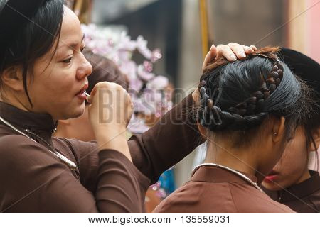 Thanh Hoa, Vietnam - October 19, 2014: Woman fixes girl's hair. They prepare for a spirit mediumship ritual of their religious community (Dao Mau) which they will be attending as guests.