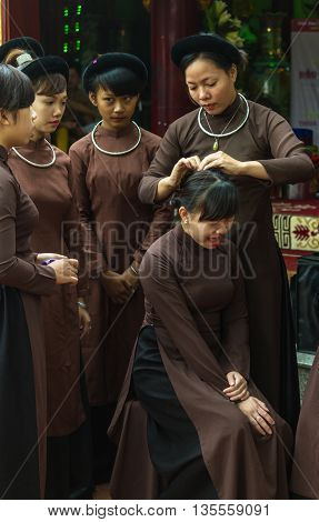 Thanh Hoa, Vietnam - October 19, 2014: A woman fixes a girl's hair. They prepare for a spirit mediumship ritual of their religious community (Dao Mau) which they will be attending as guests.