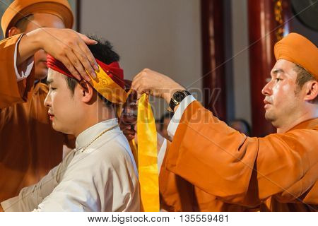 Thanh Hoa, Vietnam - October 19, 2014: A male medium is being dressed up to perform Len Dong, a spirit mediumship ritual in Central Vietnam. In trance the medium channels gods and goddesses of the Dao Mau religion.