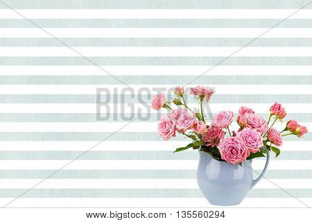 Pink flowers in blue jug on watercolor blue stripes background. Roses in jug. Postcard background. Wedding card background. Wedding invitation. Pink roses. Pink roses in blue vase with copy space.