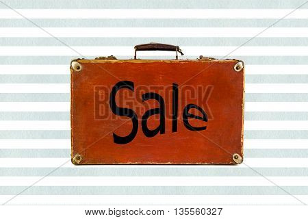 Old shabby brown suitcase on watercolor blue stripes background with sign Sale on it. Sale word on vintage travel bag. Concept sign. Sale sign on retro suitcase. Concept of discount shopping.