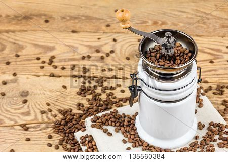 Vintage coffee grinder mill with coffee beans on wooden table .