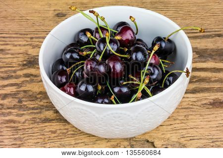 Red cherries in a white ceramic bowl on wooden background.