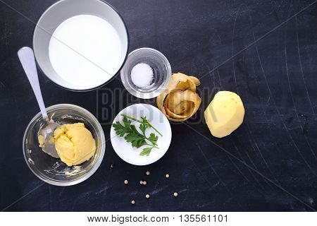Top view ingredients for mashed potatoes on black background